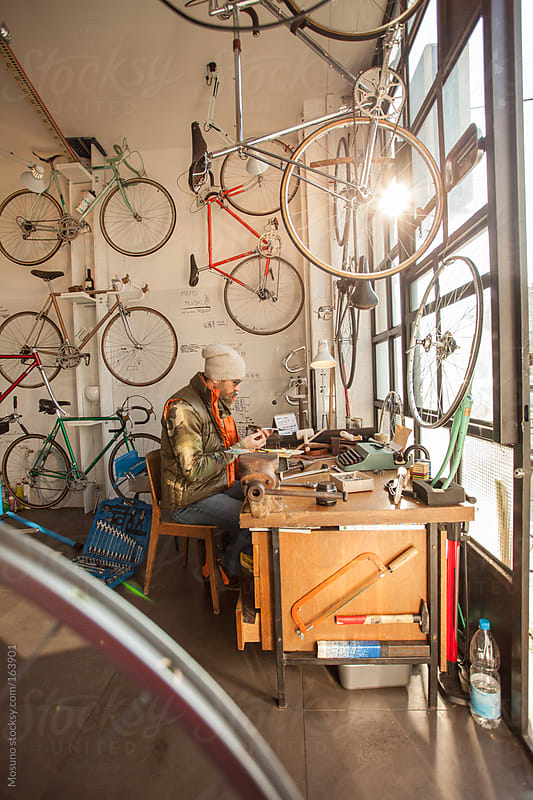 Man Working in a Bicycle Repair Shop by Mosuno for Stocksy United