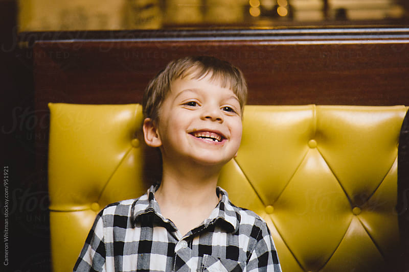 Smiling boy in a diner by Cameron Whitman for Stocksy United