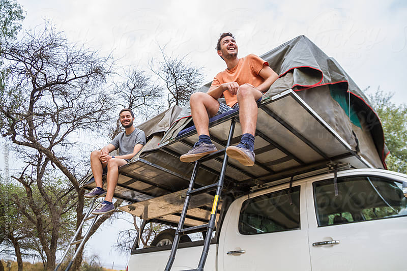 Two young happy men sitting on roof tents on top of an off-road vehicle - adventure travel by Alejandro Moreno de Carlos for Stocksy United