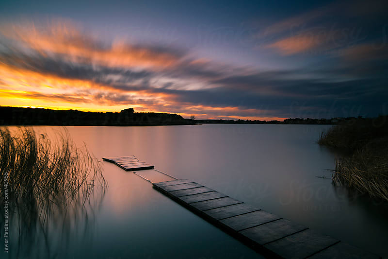 sunset on the pier of the small lake by Javier Pardina for Stocksy United