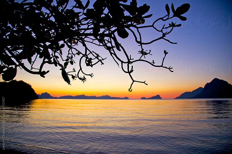 Stunning orange sunset on peaceful calm waters, Las Cabanas Beach, Palawan Island, Philippines by Jaydene Chapman for Stocksy United