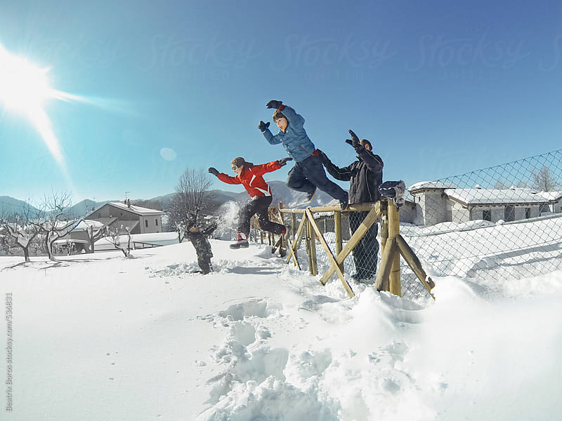 Siblings jumping from the fence into the deep snow by Beatrix Boros for Stocksy United
