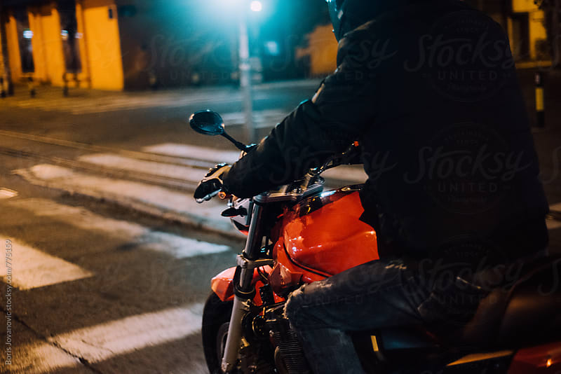 Man riding a motorbike by night by Boris Jovanovic for Stocksy United