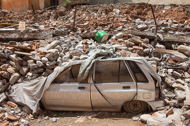 A parked car covered in debris after an earthquake. by Shikhar Bhattarai for Stocksy United