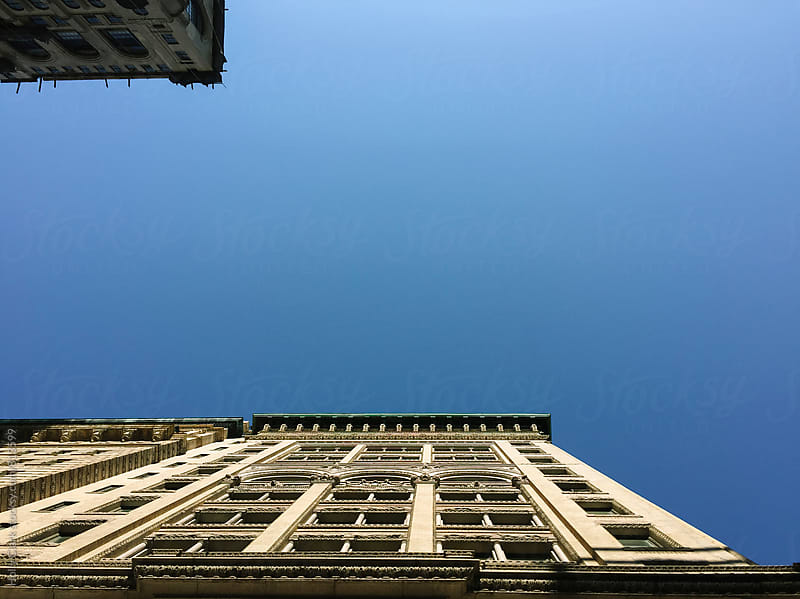 Blue sky framed by exterior of historic building by Holly Clark for Stocksy United