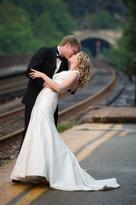 Just Married Couple Kiss on Railroad Platform by Brian McEntire for Stocksy United