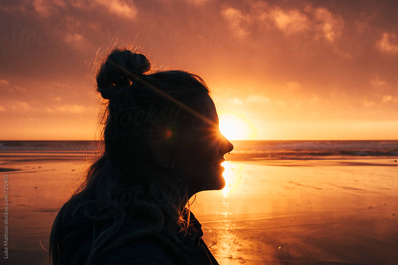 Profile Of A Young Woman's Face At Sunset On The Ocean Shore As The Sun Shines By Her Eyes by Luke Mattson for Stocksy United