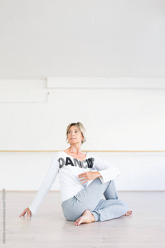 Mature woman doing twisting pose yoga by michela ravasio for Stocksy United