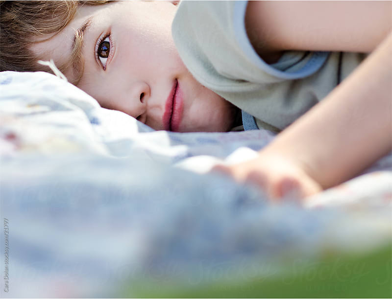 Boy rests on blanket in back yard by Cara Dolan for Stocksy United