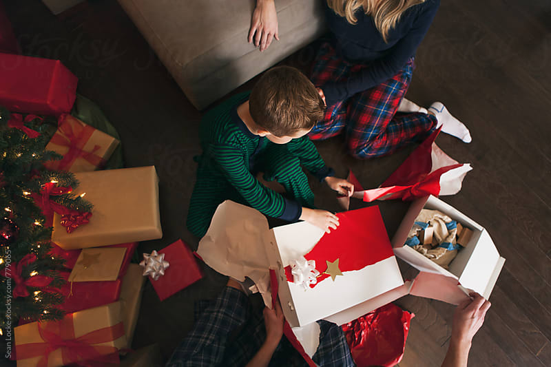 Christmas: Overhead View Of Family Unwrapping Presents by Sean Locke for Stocksy United