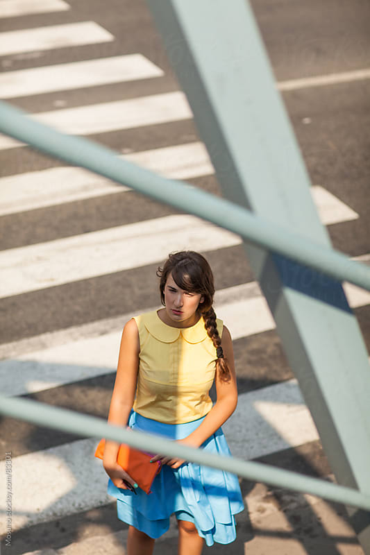 Woman crossing a road. by Mosuno for Stocksy United