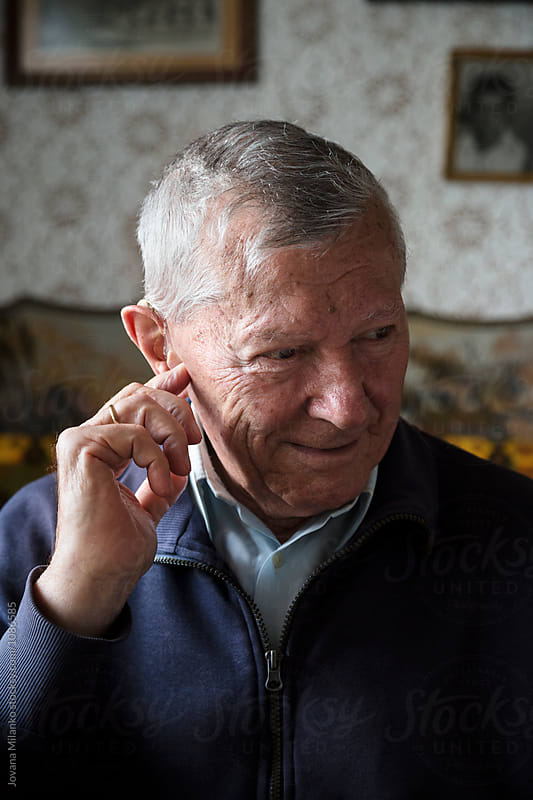 Portrait of a senior man adjusting his hearing device by Jovana Milanko for Stocksy United