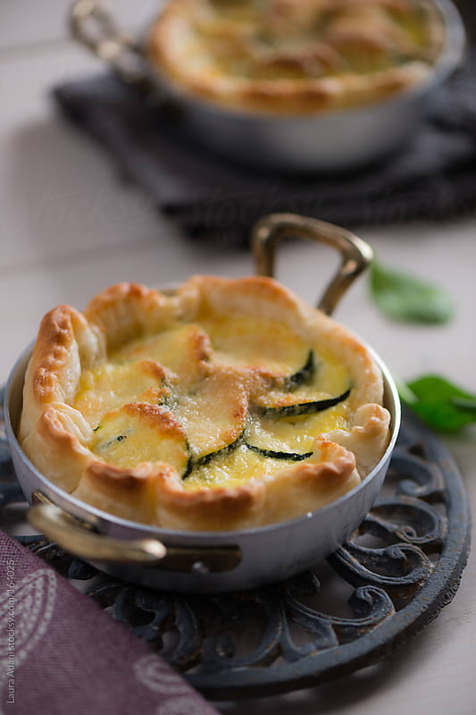 a courgette pie with eggs and cheese in a crust of pastry by Laura Adani for Stocksy United