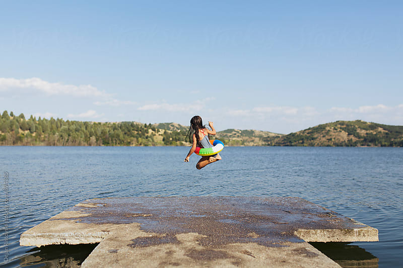 Girl jumping in lake. by Dejan Ristovski for Stocksy United