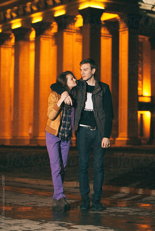 Young couple near illuminated building by T-REX & Flower for Stocksy United