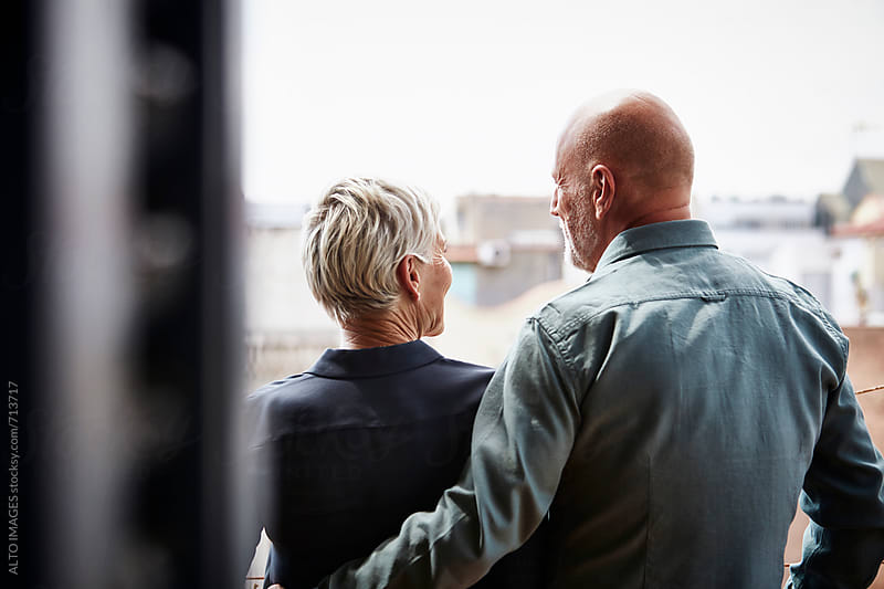Happy Senior Couple Standing On Balcony by ALTO IMAGES for Stocksy United