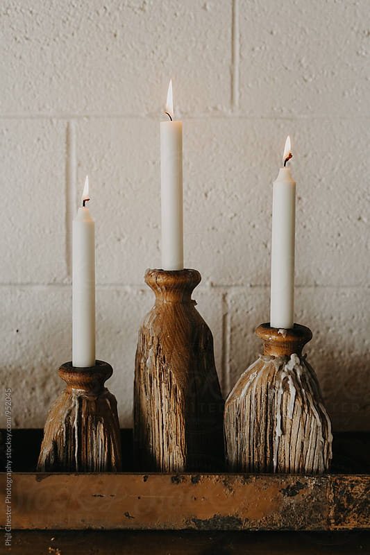 White candles burning in apartment against brick wall by Phil Chester Photography for Stocksy United