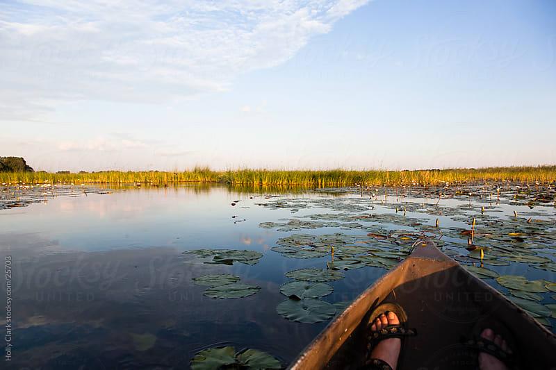 Feet Resting in a Canoe in the Okavango Delta  by Holly Clark for Stocksy United