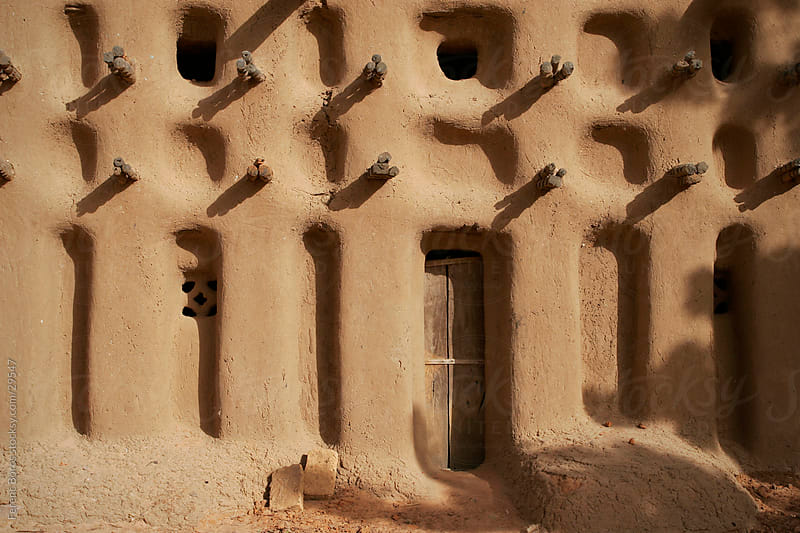 Door of an adobe mosque in Dogon country by Ferenc Boros for Stocksy United
