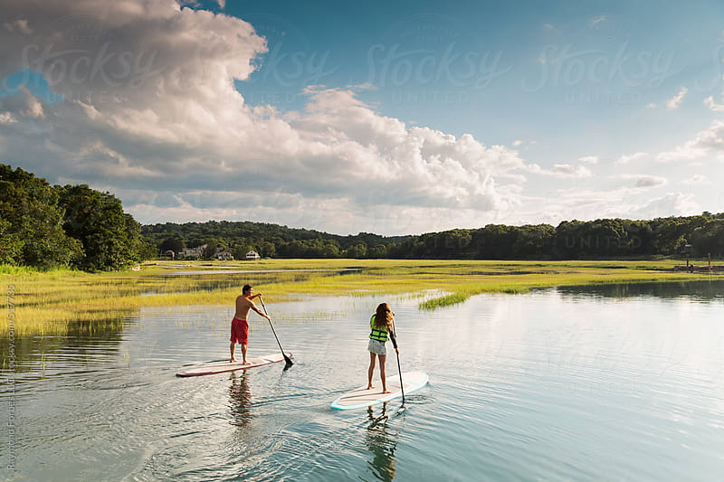 Family Paddleboarding through Marsh by Raymond Forbes LLC for Stocksy United