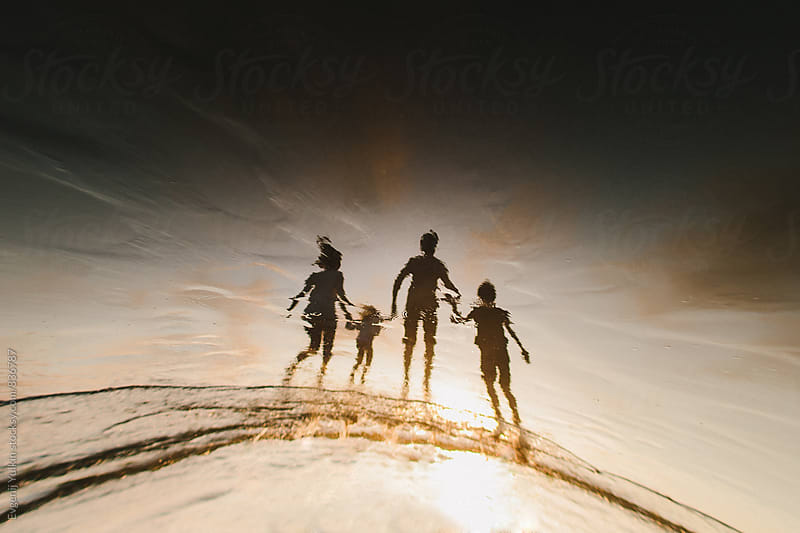 family silhouette on the sand by Evgenij Yulkin for Stocksy United