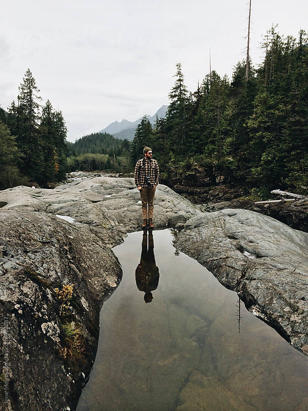 young mans reflection shows in water in nature by Jesse Morrow for Stocksy United