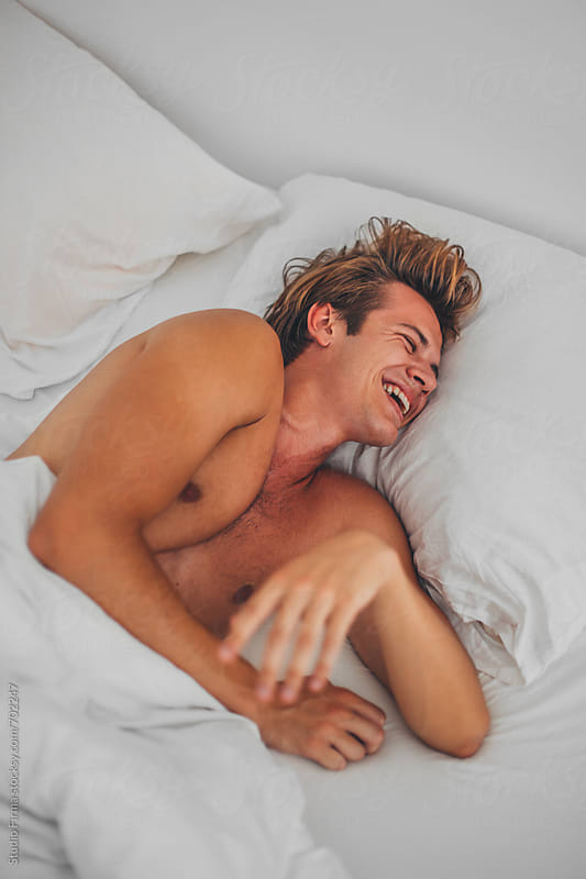 Young Man laughing in the bed. by Studio Firma for Stocksy United
