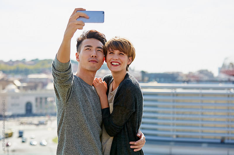 Couple Talking Selfie Through Smartphone In City by ALTO IMAGES for Stocksy United