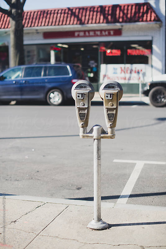 Meter in front of parking spot on a sunny day by Lauren Naefe for Stocksy United