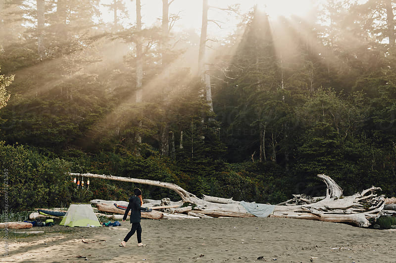 Girl on beach with tent in morning sun by Taylor Roades for Stocksy United