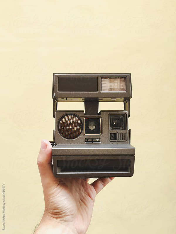 Male hand with a vintage instant camera by Luca Pierro for Stocksy United