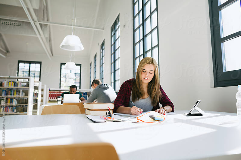 Young woman studying in a library. by BONNINSTUDIO for Stocksy United