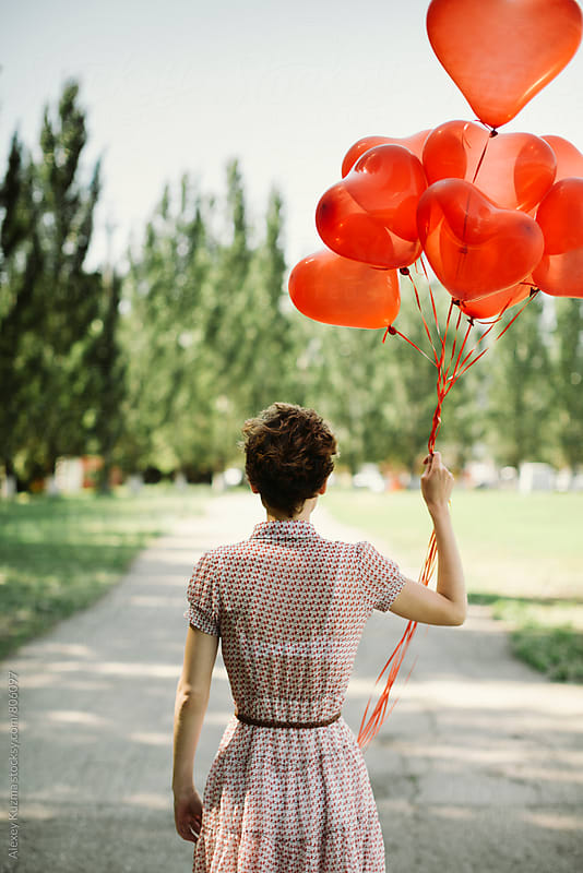 woman with red balloons by Alexey Kuzma for Stocksy United