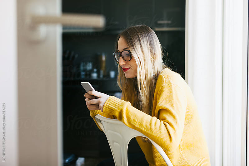 Side view of a woman using her phone at home. by BONNINSTUDIO for Stocksy United