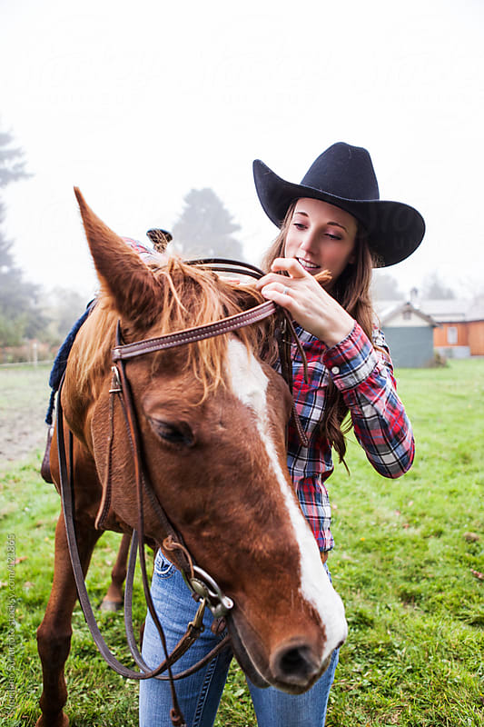 Cowgirl and her horse on the field by Suprijono Suharjoto for Stocksy United