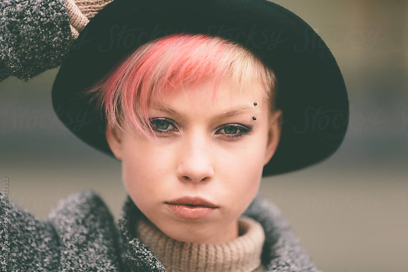 young woman with black hat and pink hair by Alexey Kuzma for Stocksy United