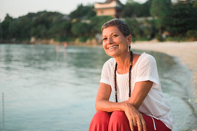 Senior Woman Sitting on a Beach by Mosuno for Stocksy United