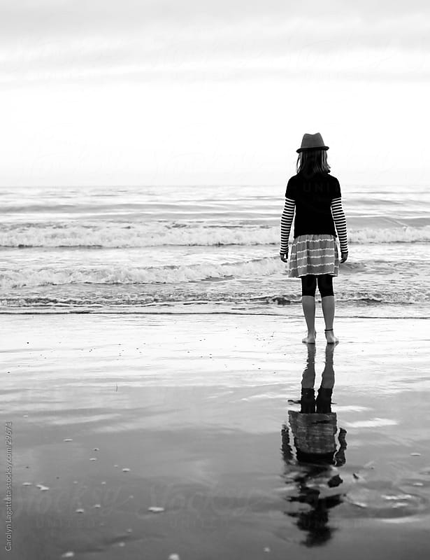 Black and white shot of a young girl staring at the ocean in a fedora by Carolyn Lagattuta for Stocksy United