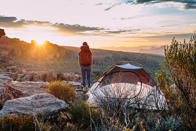 Female hiker with backpack standing outside her camp tent at sunset by Micky Wiswedel for Stocksy United