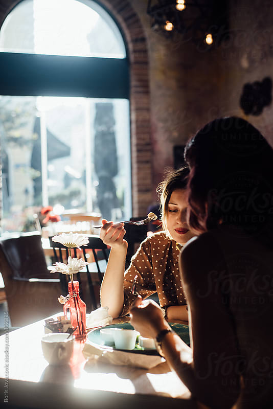 Two women having a breakfast in the restaurant  by Boris Jovanovic for Stocksy United