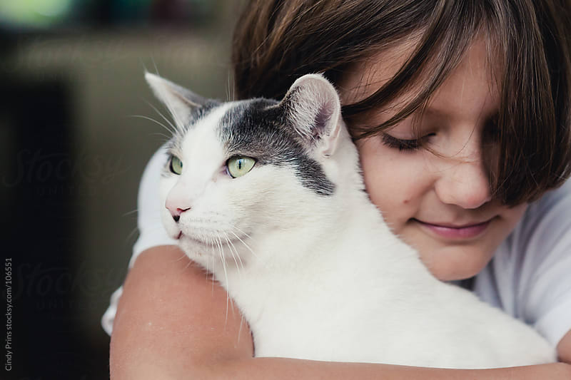 Boy hugging his cat by Cindy Prins for Stocksy United