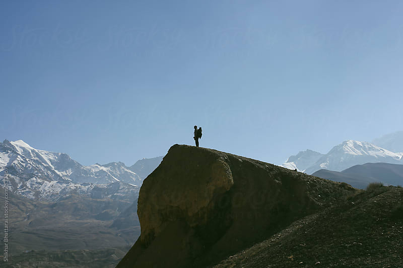 A traveller standing atop a hill watching the scenic view of the himalayas. by Shikhar Bhattarai for Stocksy United