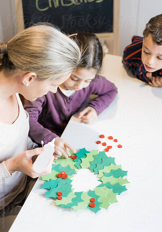 A mother teaching her children to make Christmas decoration craf by Guille Faingold for Stocksy United