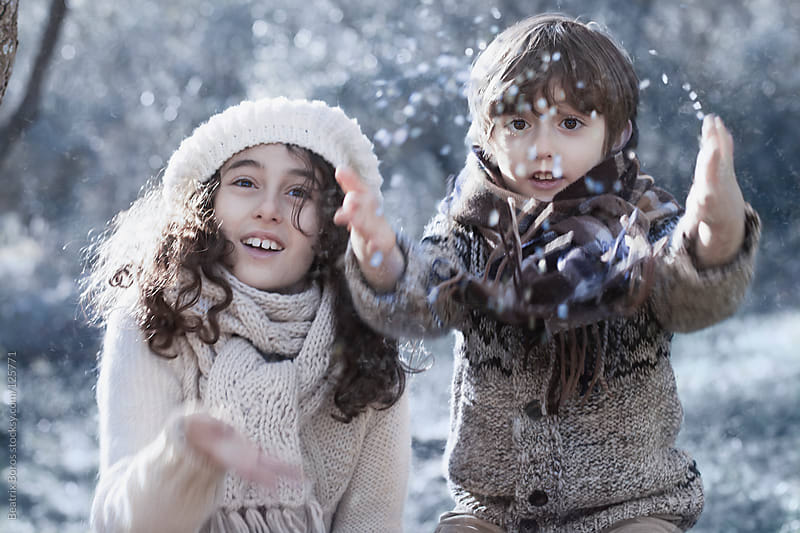 Girl and boy playing in the snow in Winter  by Beatrix Boros for Stocksy United