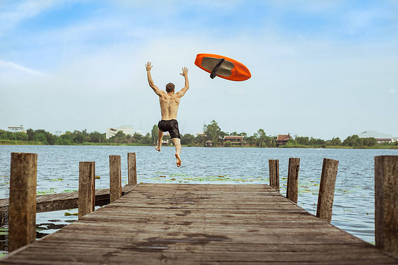 Young man jumping into the lake from a wooden pier by Jovo Jovanovic for Stocksy United