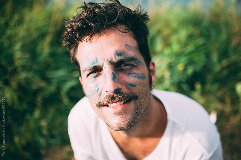 man with blue stains on his face by Thais Ramos Varela for Stocksy United