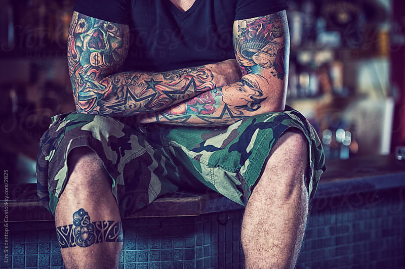 Tattooed man in bar  by Urs Siedentop & Co for Stocksy United