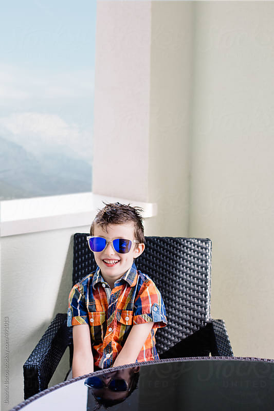 Boy sitting in an armchair on the balcony by Beatrix Boros for Stocksy United
