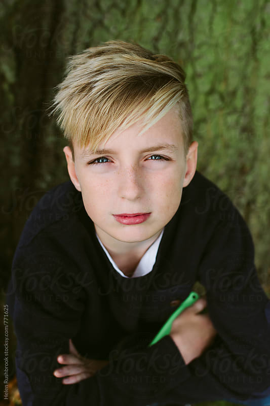 Portrait of a teenage boy sitting under a tree. by Helen Rushbrook for Stocksy United