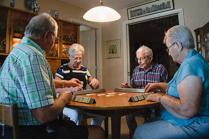 Group of seniors playing games together inside by Rob and Julia Campbell for Stocksy United